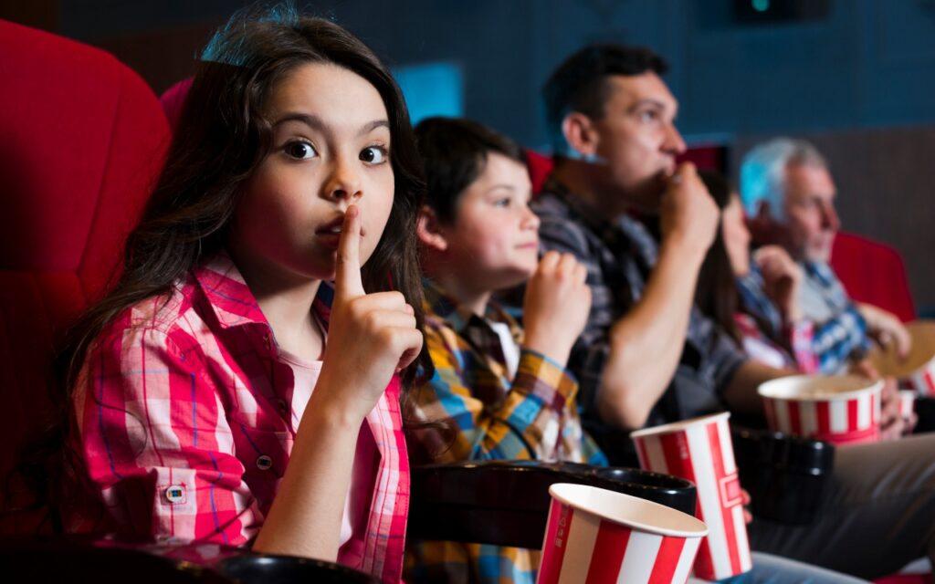 criatividade e inovação - família no cinema, filha fazendo sinal de silêncio
