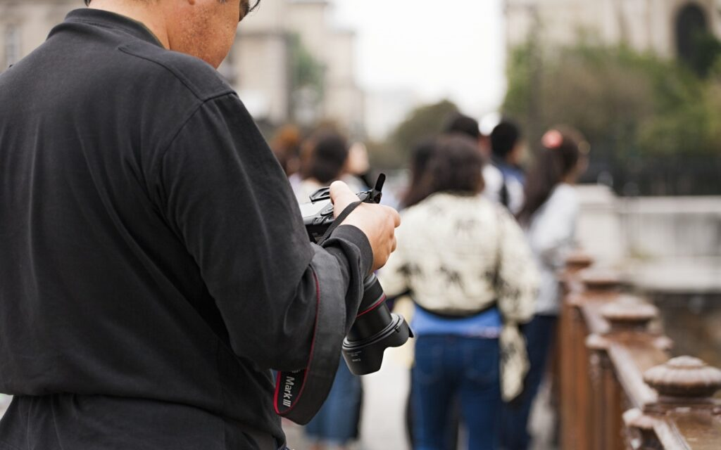 marketing de guerrilha - fotógrafo olhando para a tela de sua câmera, pessoas andando ao fundo
